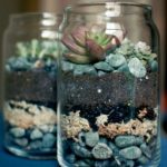 Jar filled with stones, dirt, and succulents.