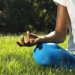 A photo of a person meditating in the grass.