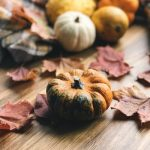 A photo of small pumpkins and gourds on a table with autumn leaves.