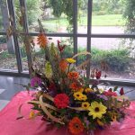 A photo of a floral arrangement with purple, yellow, orange, and red flowers.
