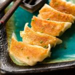 A photo of delicious gyoza on a stone plate.
