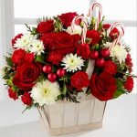 A photo of a floral arrangement with red and white flowers and christmas bulbs.