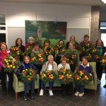 A group of class participants posing with their wreaths made in class.