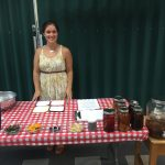 Photo of a woman standing at a table making kombucha.