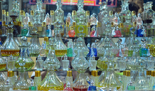 This is an image of many vintage glass perfume bottles. The bottles contain a variety of brightly colored fragrances.