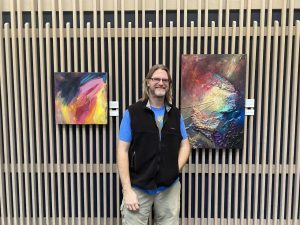 This is an image of the artist Daniel Kathalynas standing in front of two bright and colorful paintings