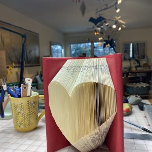 The image is of a book. The pages of the book have been folded into a heart.
