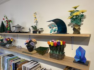 The image shows shelves in the artist's studio displaying many books and pieces of paper art